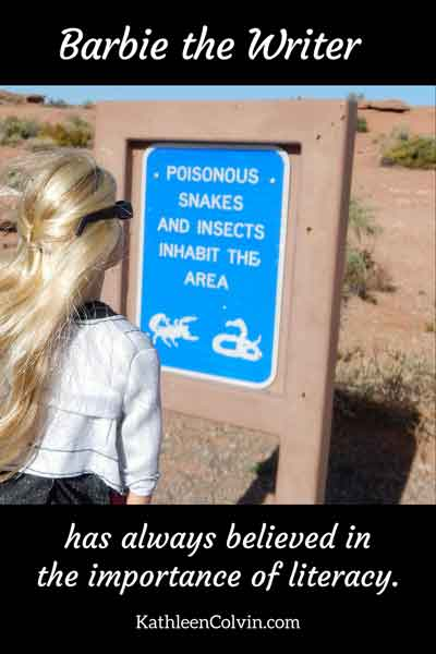 "Barbie reading a sign posted in a desert area: ""Poisonous Snakes and Insects Inhabit This Area."" Barbie the writer has always believed in the importance of literacy. By Kathleen Colvin."
